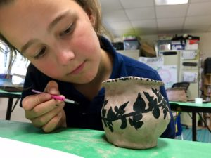 An Intermediate School student works on painting a Greek vase during Art class. For IS students, art lessons are connected to their Humanities curriculum.